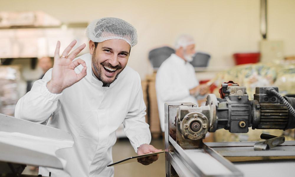 Optimierung von Instandhaltungs- und Qualitätssicherungsprozessen. Mann signalisiert sehr gute Qualität mit Handbewegung, in der anderen Hand hat er ein Touchscreen-Tablet.