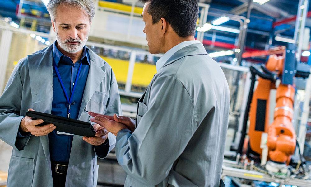 Leistungs- und Kostenüberwachung durch uControl: zwei Ingenieure diskutieren in einer Produktionshalle.