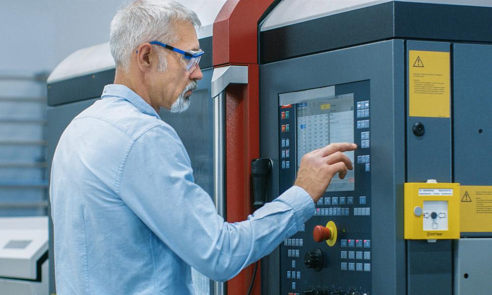 uControl_Produktionscontrolling_ConditionMonitoring: Chefingenieur bedient ein modernes Überwachungstool