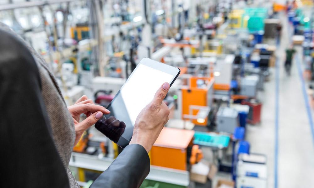 konfigurierbare Dashboards für nutzerspezifische Ansichten und Auswertungen: Frau überwacht mit Touchscreen-Tablett eine große Produktionshalle